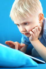 Obraz Przedszkolak gra w gry na tablecie cyfrowym - fototapety do salonu
