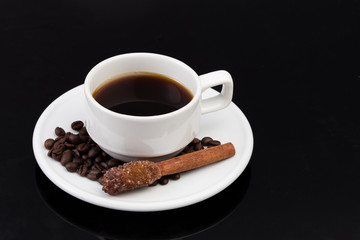 Cup of coffee with sugar stick, on black with clipping path