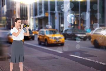 Serious elegant businesswoman looking through binoculars