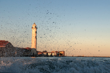 Water splash with lighthouse background