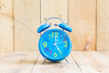 Alarm Clock , in blue, showing five o'clock
