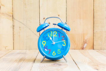 Alarm Clock isolated on white, in blue, showing eleven o'clock