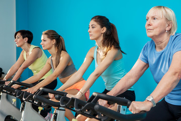 Four women are cycling at the fitness center