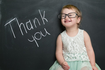 Little girl at the blackboard with the words thank you