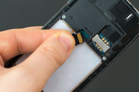 Male hand inserting Micro SD card to mobile phone.