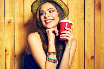 Smiling Hipster Girl Holding Coffee Cup. Yellow hat.