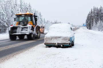 Traktor driving broken and abandoned on roadside car in snow and ice. Winter highway in north of Russia