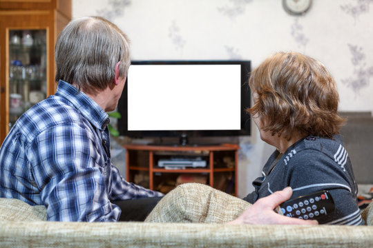 Senior couple sit front of TV, watching isolated white screen
