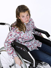 Girl sat in a wheelchair, on white background