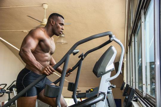 Muscular black male bodybuilder exercising on step machine