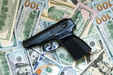black gun against the background of US dollars