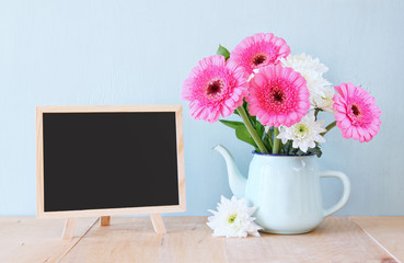 summer bouquet of flowers on the wooden table and blackboard wit