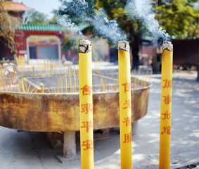 Burning incense sticks on background of the main entrance to the