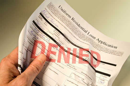 Denied loan application crumpled in hand