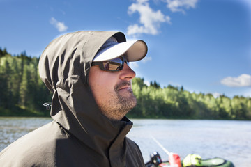 Portrait of a fisherman on a background of the river