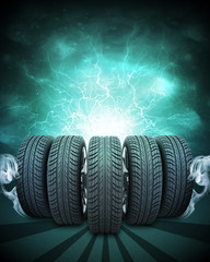 Wedge of new car wheels. Green background is night sky and