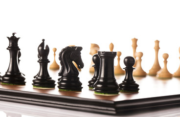 Loose standing black and white chess pieces on a table