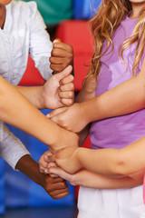 Kinder bauen Turm mit Händen und Fäusten