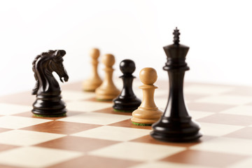 black chess knight against the mixed chess pices