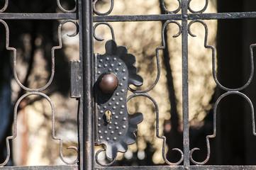 Lock on metal grid on closed black patio door closeup