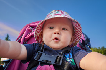 Baby in the park taking his first selfie with an amazed and exci