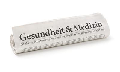 Zeitungsrolle mit der Überschrift Gesundheit und Medizin