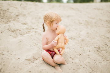 Toddler girl at the beach kissing her baby doll