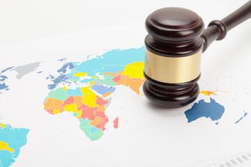 Foto op Plexiglas Wereldkaart Wooden judge's gavel over colorful world map
