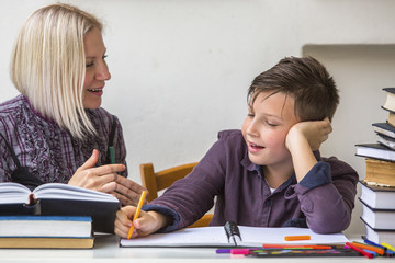Junior student does homework with the help of his tutor..