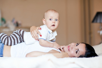 Mother are lovely playing  with baby in bed