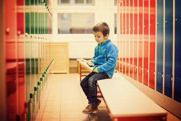 Cute boy in a locker room, sitting on a bench