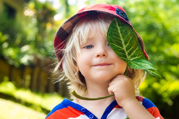 Cute happy child holding a leaf over his eye