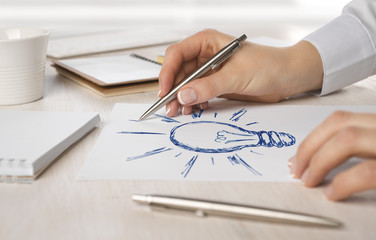Business woman hand drawing on paper a light bulb