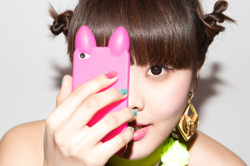 Chica joven oriental mirando a través de su movil