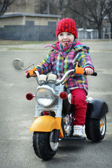 In the spring a little girl riding a motorcycle.