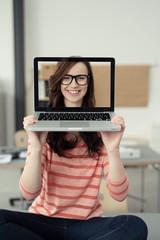 junge frau hält laptop vor ihr gesicht