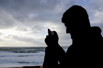 black shape of a man taking a picture of the landscape of sea an