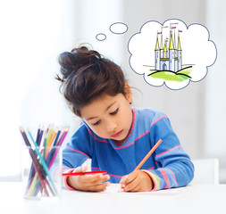 happy little girl drawing castle with crayons