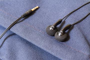 black earbud on blue canvas bag