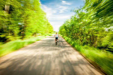 Blurred motion of woman riding bicycle in countryside