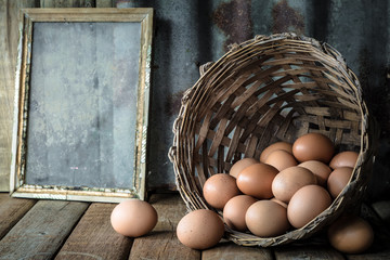 Still life with eggs in bamboo basket on wood table with rusty s