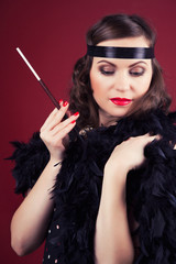 beautiful retro woman holding mouthpiece against wine red backgr