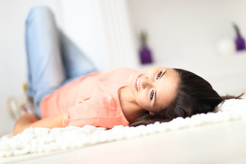 Relaxed woman lying on the floor indoors