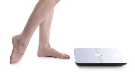 Bare Feet of a Woman Beside Body Analyzer Device
