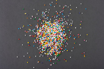 Fototapete - Colorful round sprinkles spilled on black background, isolated