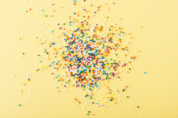 Fototapete - Colorful round sprinkles spilled on yellow background, isolated
