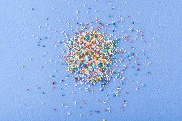 Fototapete - Colorful round sprinkles spilled on blue background, isolated