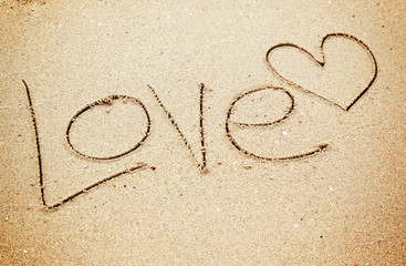 Love text and heart drawn on sand