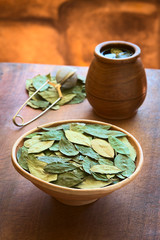 Dried coca leaves in clay bowl with fresh coca tea
