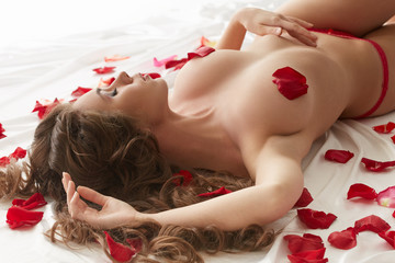 Topless beauty lying in petals of roses